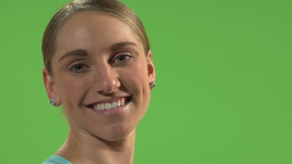 Young woman smiling in front of green screen.