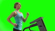 Young woman running on the treadmill in front of green screen.