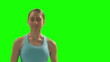 Woman running on the treadmill, facing camera. Green screen.