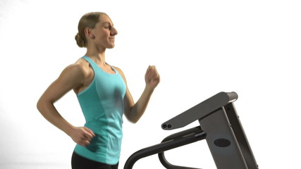 Young woman running on the treadmill. White background.