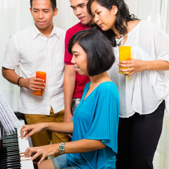 Asian people sitting together at the piano
