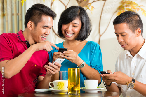 Asian people having fun with mobile phone