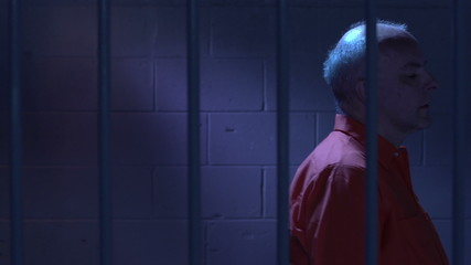 Man behind bars pacing back and forth in his cell