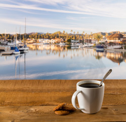 Coffee mug on wood table by harbor
