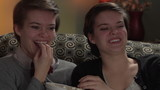 Twin sisters watching a comedy together eating popcorn