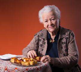 Senior woman tasting apple pie on an orange background
