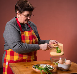 Woman preparing salad  on an orange background