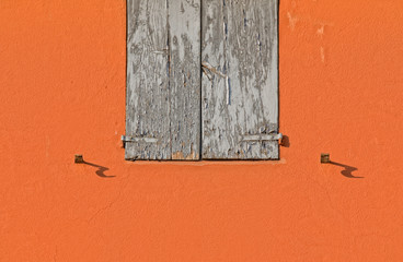 Part of a closed old wooden shutters on an orange wall