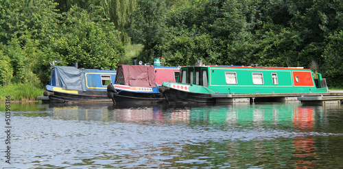 Three Narrow Boats at a Canal Mooring Point.