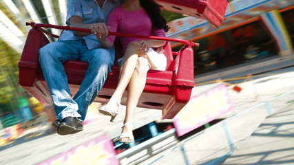 Young couple spinning on a carousel in amusement park