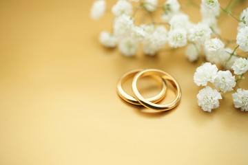 Gold wedding rings with flowers and copy space