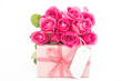 Bouquet of beautiful pink roses next to a pink gift with an empt