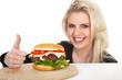 Hübsche junge Frau mit Hamburger lacht Daumen hoch