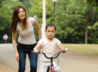 chinese mother having good time on bicycle with her daughter