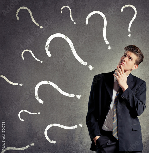 Businessman thinking, question marks on a wall