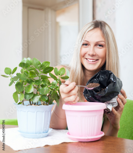 Smiling woman transplants Kalanchoe plant
