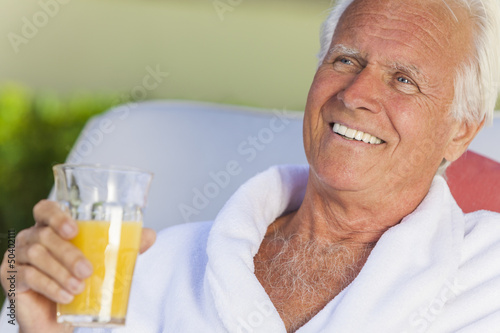 Senior Man In Bathrobe Drinking Orange Juice