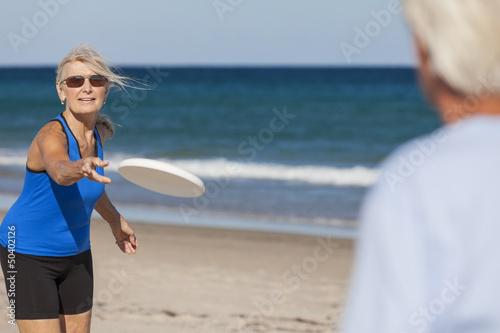 Senior Man Woman Couple Frisbee at Beach