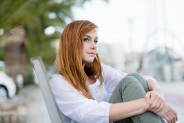 junge frau sitzt auf einer bank in der stadt