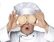 Gracioso cocinero sujetando dos bizcochos de arroz.