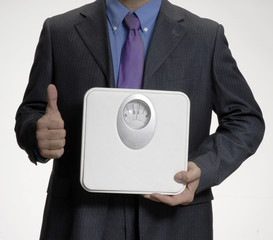 Ejecutivo optimista sujetando una balanza de peso.