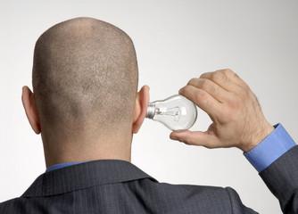 Ejecutivo colocando una bombilla en el oído,concepto negocios.