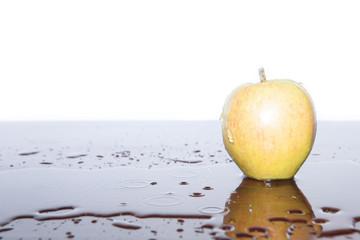Apfel in Wasserpfütze mit Wasserspritzer am Apfel