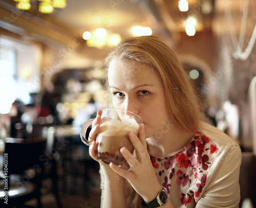 Girl is drinking latte in cafe.