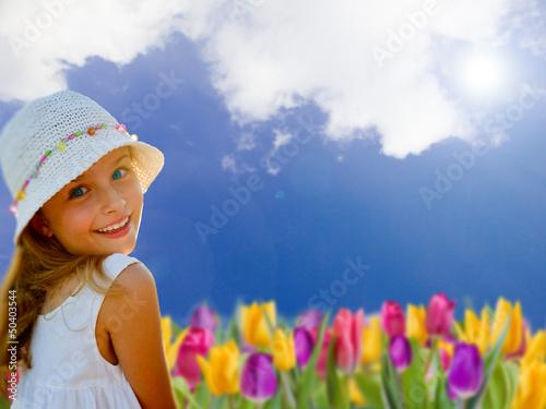 Spring garden, tulips -portrait of lovely girl  in the garden
