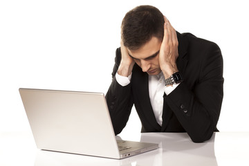 desperate young man leaning on both hands behind his laptop