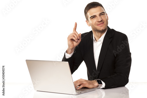 attractive businessman shows his finger up behind his laptop