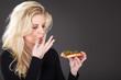 Junge blonde Frau isst Pizza und leckt sich die Finger