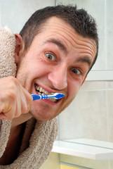 Hombre joven cepillando los dientes,lavando los dientes.