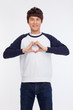 Young Asian man showing heart shape.