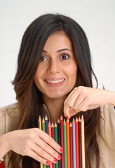 Joven estudiante sujetando varios lápices.