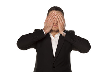 businessman in black suit, covering his eyes with a fist