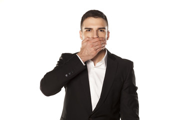 businessman in black suit, covering his mouth with his hand