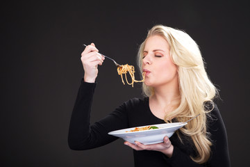 Junge blonde Frau isst Spaghetti und schlürft
