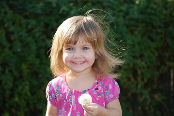 Young girl holding dandelion