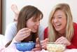 Dos amigas disfrutando y comiendo palomitas de maíz.