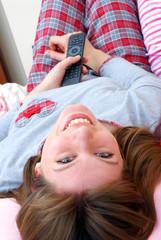 Joven mujer feliz recostada en su cama viendo televisión.