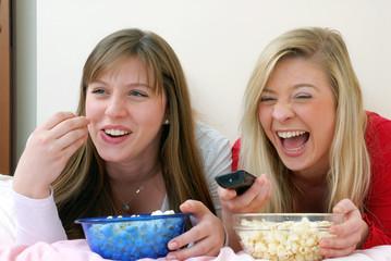 Dos amigas disfrutando y comiendo palomitas de maíz.viendo tv