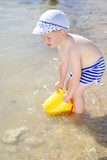 a little boy playing on the sea-shore in summer
