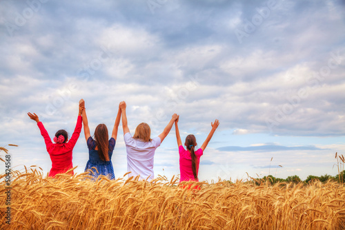 Four young people staying with raised hands