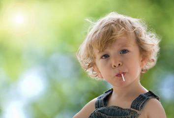 Portrait eines kleinen Jungen auf sonnig-grünem Hintergrund