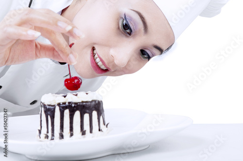 Beautiful chef decorating cake