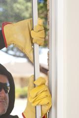 Burglar breaking through window of home