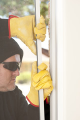 Thief breaking through window of home