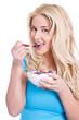 Junge blonde Frau isst genüsslich ihr Müsli