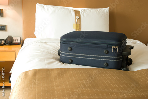 suitcase on bed inside a hotel room